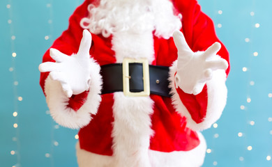 Santa with holding gesture on a shiny light blue background