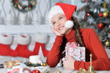 Portrait of beautiful happy girl in Santa hat sitting with Christmas present