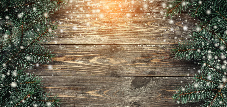 Old wood background with fir branches. Space for a greeting message. Christmas card. Top view. Effect of light and snowflakes.