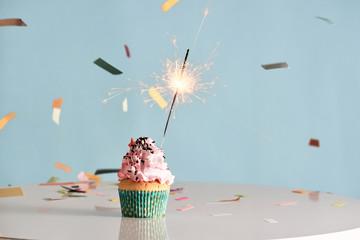 Single sparkler on cupcake blue wal
