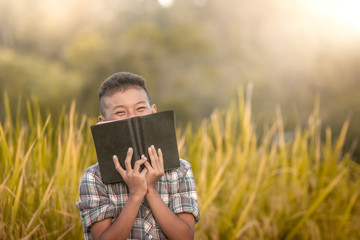 Happy boy. holding bible and standing in rice field. Wall mural