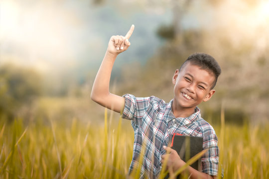 Happy boy standing in rice field. holding bible and saying one way jesus.