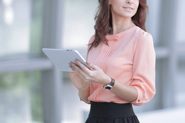 confident business woman with digital tablet on blurred office background.
