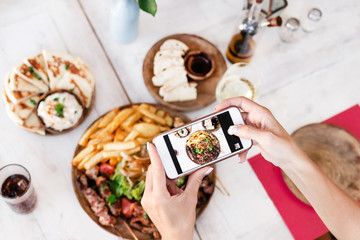 Woman taking photo of mix grill dish using smartphone in restaurant. Bali island. Indonesia.