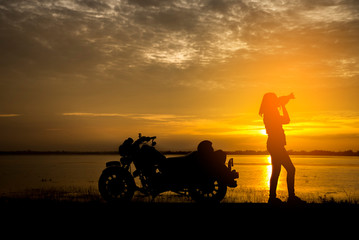 Travel of Photographer woman,Silhouette of Biker take photo beside motorbike with dslr camera.People side view,Young traveler girl sightseeing with beautiful sunset background in Thailand.