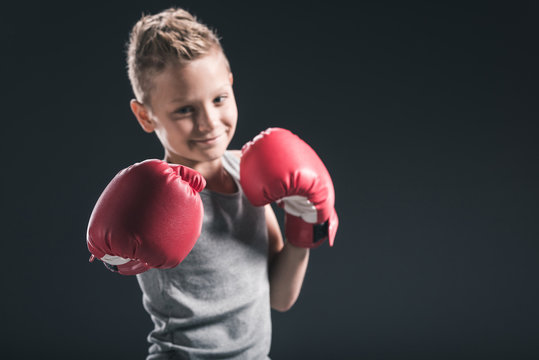 portrait of smiling boy with red boxing gloves on black backdrop