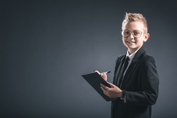 smiling preteen boy in businessman suit and eyeglasses with notepad on grey background