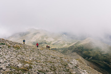 Unrecognizable people walking in mountains