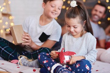 Adorable girl opening christmas present in bed