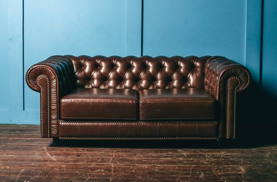 luxurious leather, brown sofa, blue wall. classic vintage furniture.
