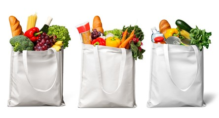 Shopping bags with groceries isolated on white