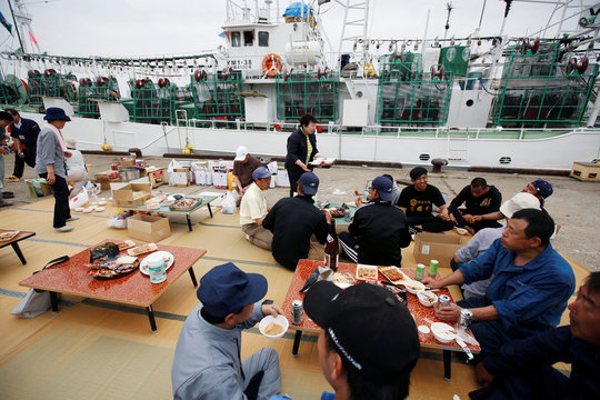 Relatives and crew members of squid fishing ship Hosei-Maru No.58 hold the small party before the departure of the ship for fishing at a port in Sakata