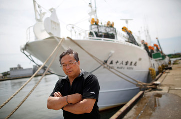 Shigeru Saito, captain of the squid fishing ship Hosei-Maru No.58, poses for a photograph in front of his ship at a port in Sakata