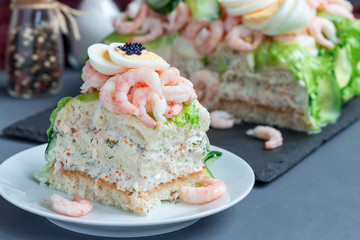 Piece of traditional savory swedish sandwich cake Smorgastorta with bread, shrimps, eggs, caviar, dill, mayonnaise, cucumber and lettuce, horizontal