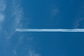 Distant plane leaving a contrail in the sky.