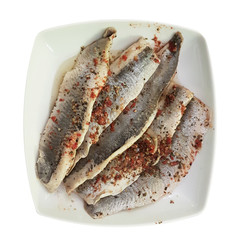 A dish of salted fish fillet in oil and seasonings on a plate. Food on a white isolated background. Restaurant menu and diner. Cooking fish. Source of Omega 3 acids and fats for the body. Diet food