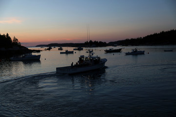 A lobster boats pulls out of the harbour at sunrise in Stonington