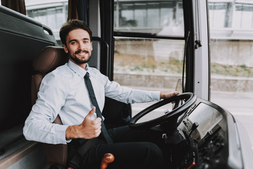 Smiling Man Driving Tour Bus. Professional Driver