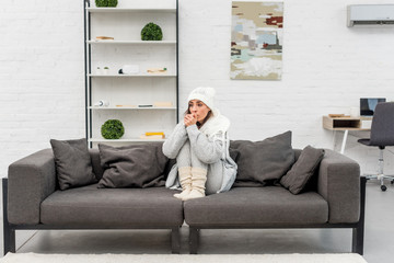 freezed young woman in warm clothes sitting on sofa at home