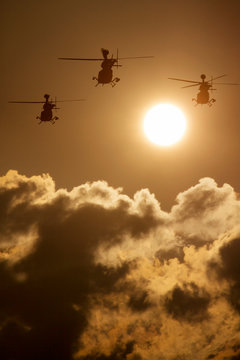 This photo illustration depicts three military helicopters flying towards a rising sun. The clouds also appear like smoke rising from below.