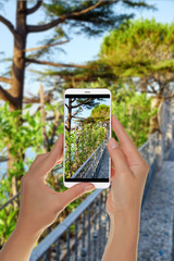 A tourist is taking a photo of path in mountains with vineyards on a mobile phone