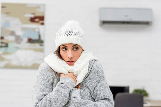 close-up portrait of freezing young woman in warm clothes with air conditioner on background