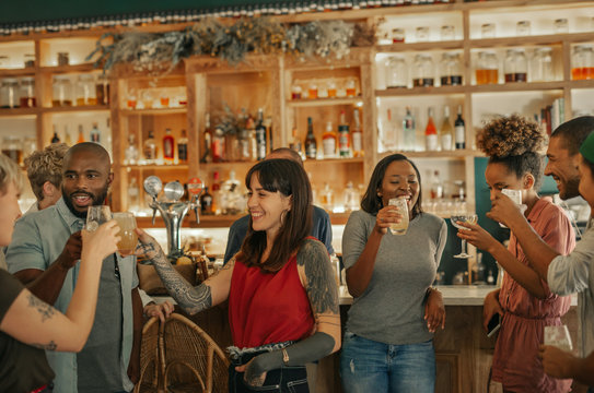 Diverse group of people drinking together in a trendy bar
