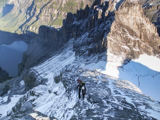 mountain climber rappelling from a high rocky mountain peak in the Swiss Alps near Kandersteg