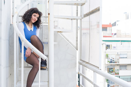 Portrait of a beautiful smiling young woman in an elegant dress sitting on a metal stairs.