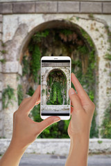 A tourist is taking a photo of a small cave overgrown with ivy near Terrazza del Pincio. Rome, Italy on a mobile phone