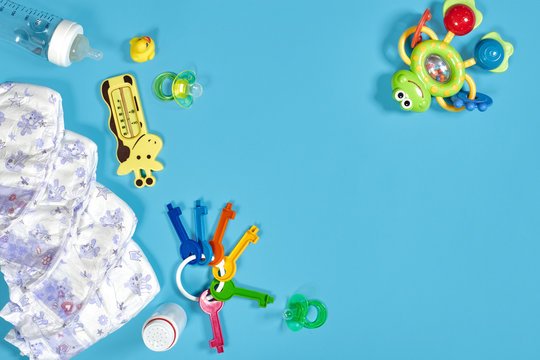 Babies goods: cloth diaper, baby powder, nibbler, cream, teether, soother, baby toy on blue background. Copy space. Top view.