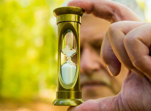 eine Sanduhr in der Hand eines Mannes symbolisiert das Verrinnen der Zeit