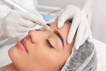 Young woman undergoing procedure of permanent eyebrow makeup in tattoo salon, closeup