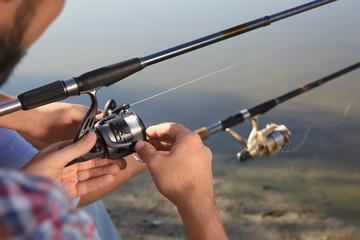 Men fishing at riverside on sunny day, closeup