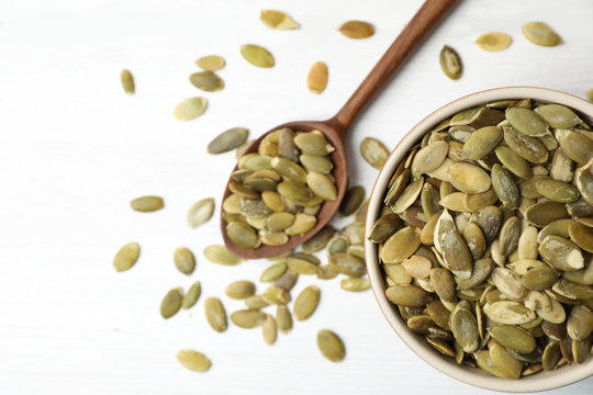 Shelled raw pumpkin seeds in dish on white background, top view