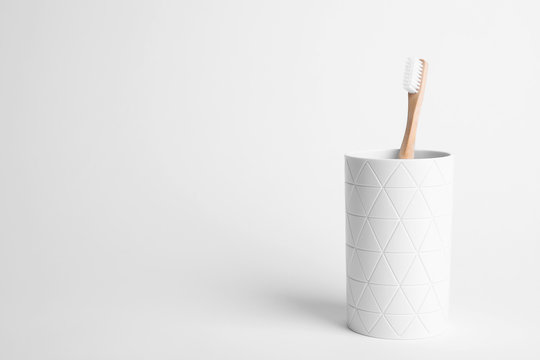 Holder with eco bamboo toothbrush on white background. Space for text