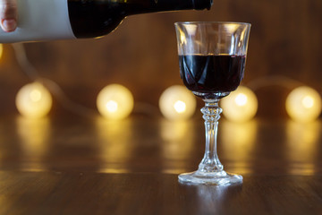 Red wine pouring into crystal glass
