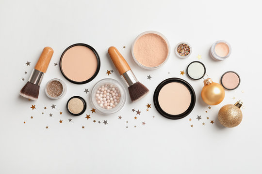 Flat lay composition with makeup products and Christmas decor on white background