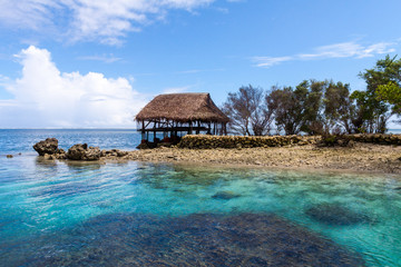 Traditional bungalow of native aborigines Micronesian people. Reef coral island motu. Blue azure turquoise lagoon with corals. Pohnpei island, Micronesia, Federated States of Micronesia (FSM), Oceania