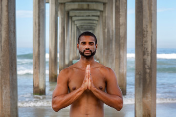 Athletic Man in Yoga Prayer Pose on the Beach with Eyes Open