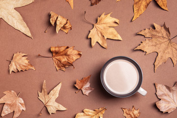 Flat lay composition with hot cozy drink and autumn leaves on color background