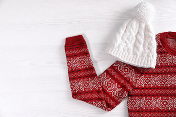Knitted hat and Christmas sweater with pattern on wooden background, top view. Space for text