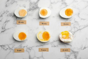 Various types of boiled eggs on marble background, flat lay. Cooking time