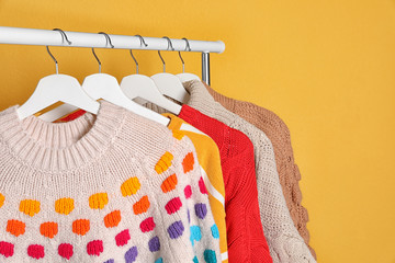 Fototapete - Collection of warm sweaters hanging on rack against color background. Space for text