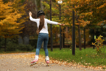 Cute girl roller skating in autumn park