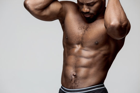 Fit young man with beautiful torso, isolated on gray background. The naked torso of African American man posing at studio. The muscular body, fitness, sports, healthy lifestyle and bodybuilder concept