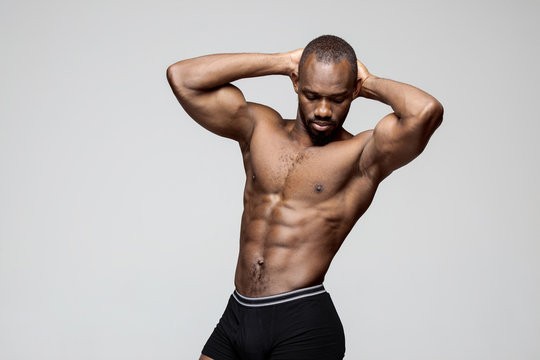 Fit young man with beautiful torso, isolated on white background. The naked torso of African American man posing at studio. The muscular body, fitness, sports, healthy lifestyle and bodybuilder