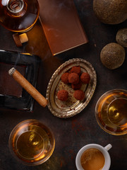 Still life with cognac glasses, cigar and pralines