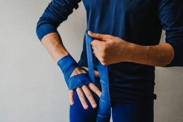 .Young sportsman man preparing bandages for his hands to start boxing. Sportwear in colour blue. Lifestyle..