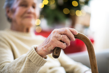A close-up of a senior woman holding a walking stick at home at Christmas time.